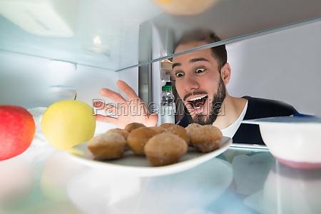 excited, man, looking, at, cookie - 23610320