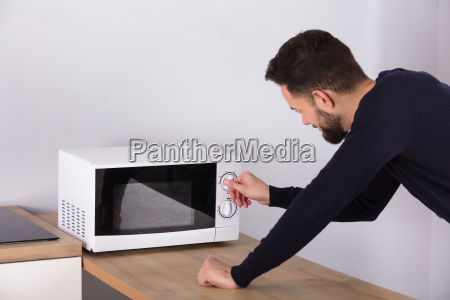 man, preparing, food, in, microwave, oven - 23610354