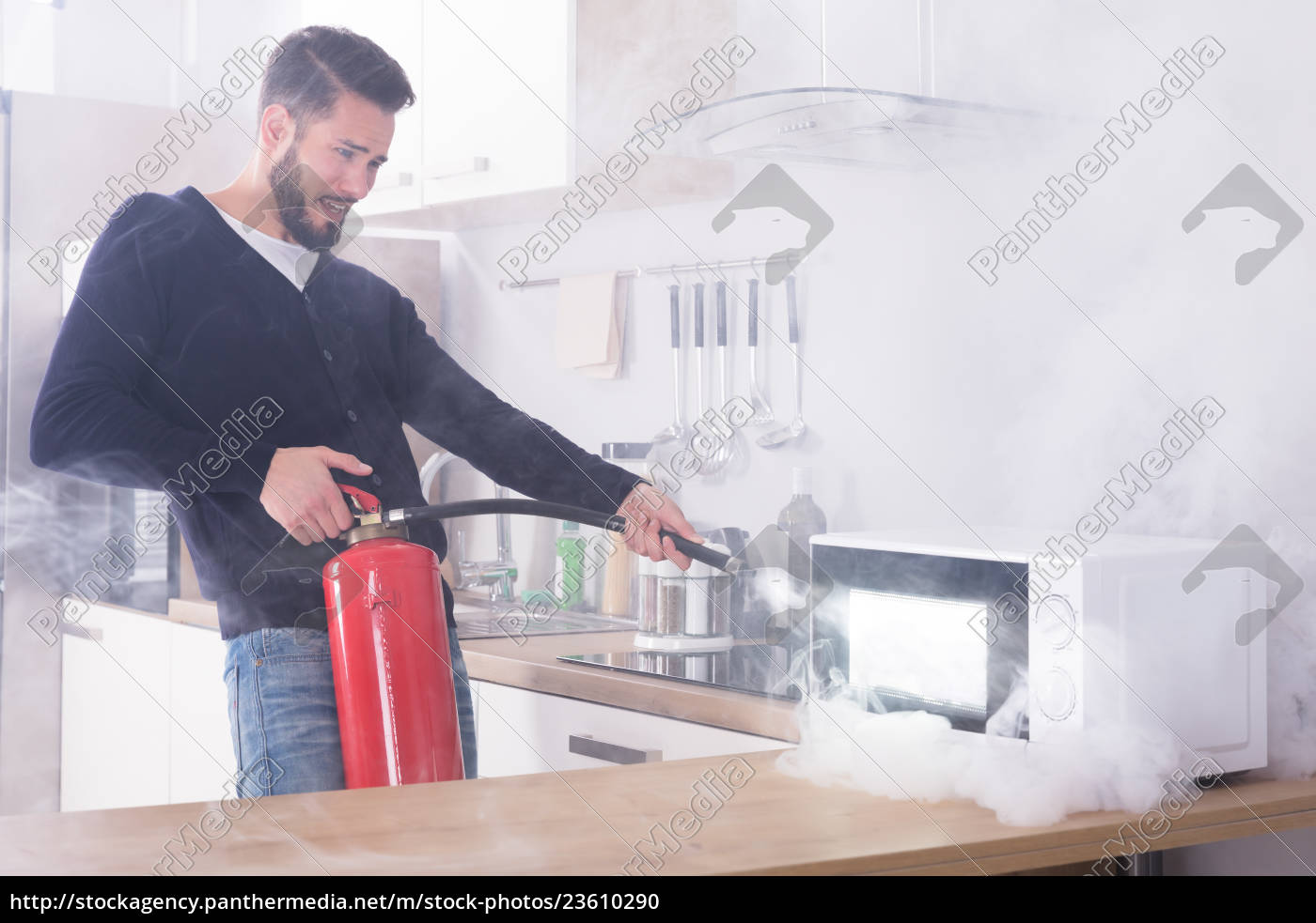 man, spraying, fire, extinguisher, on, microwave - 23610290