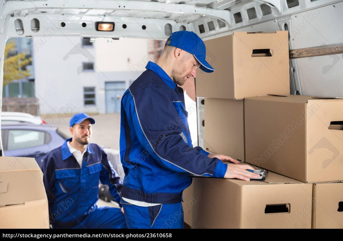 mover, looking, at, his, partner, writing - 23610658