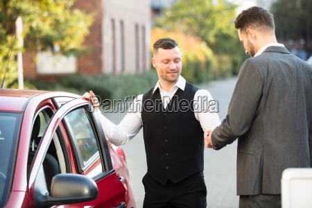 smiling, valet, and, businessperson, standing, near - 23610210