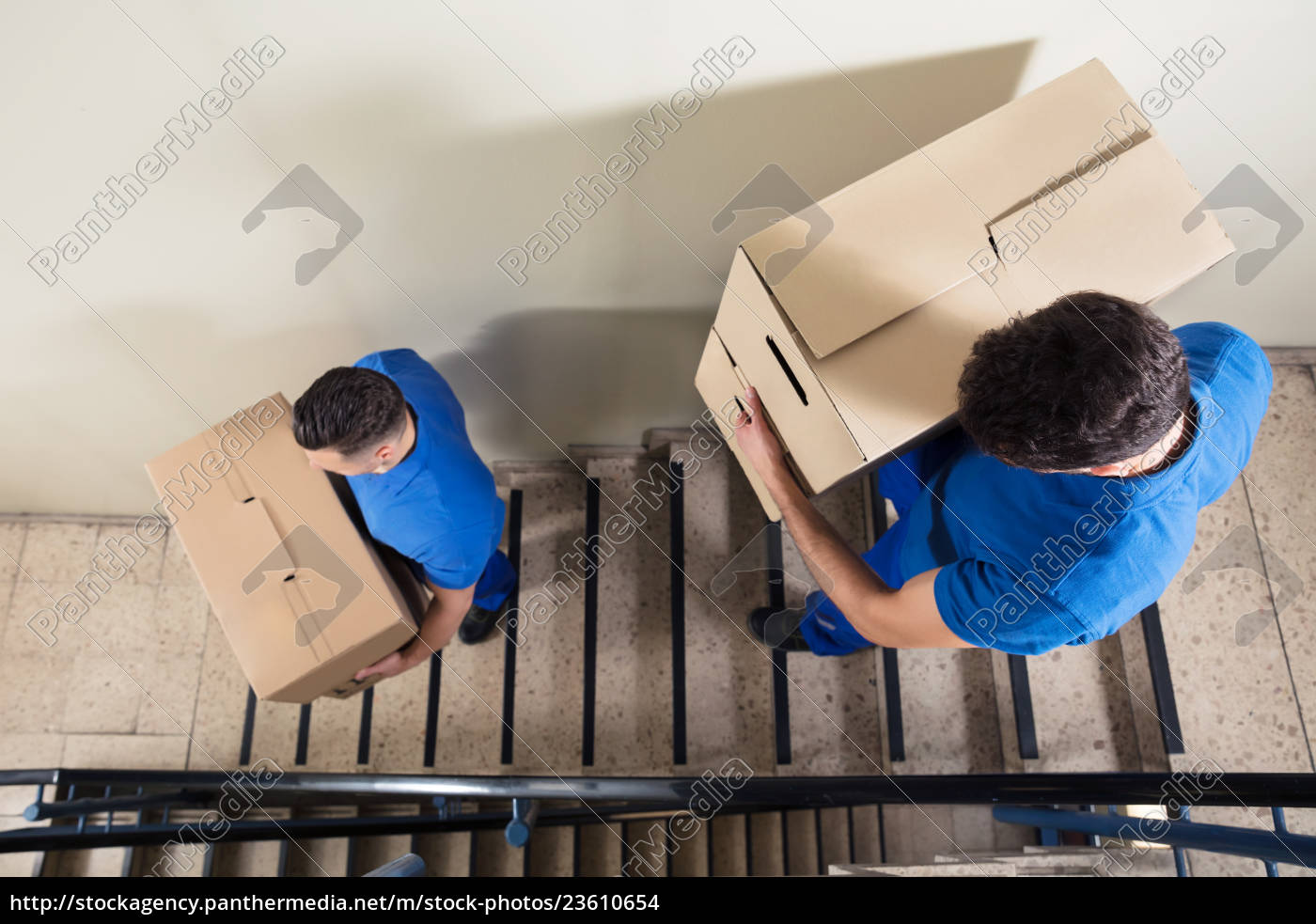 two, movers, carrying, cardboard, boxes, on - 23610654