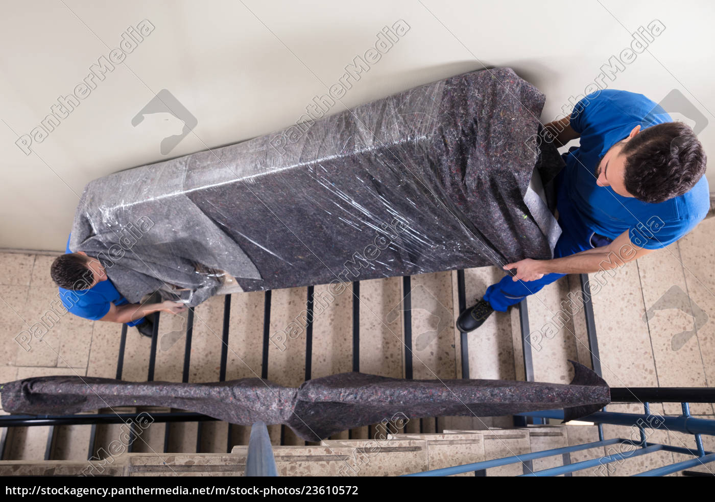 two, movers, carrying, furniture, on, staircase - 23610572