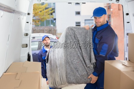 two, movers, unloading, furniture, from, truck - 23610660