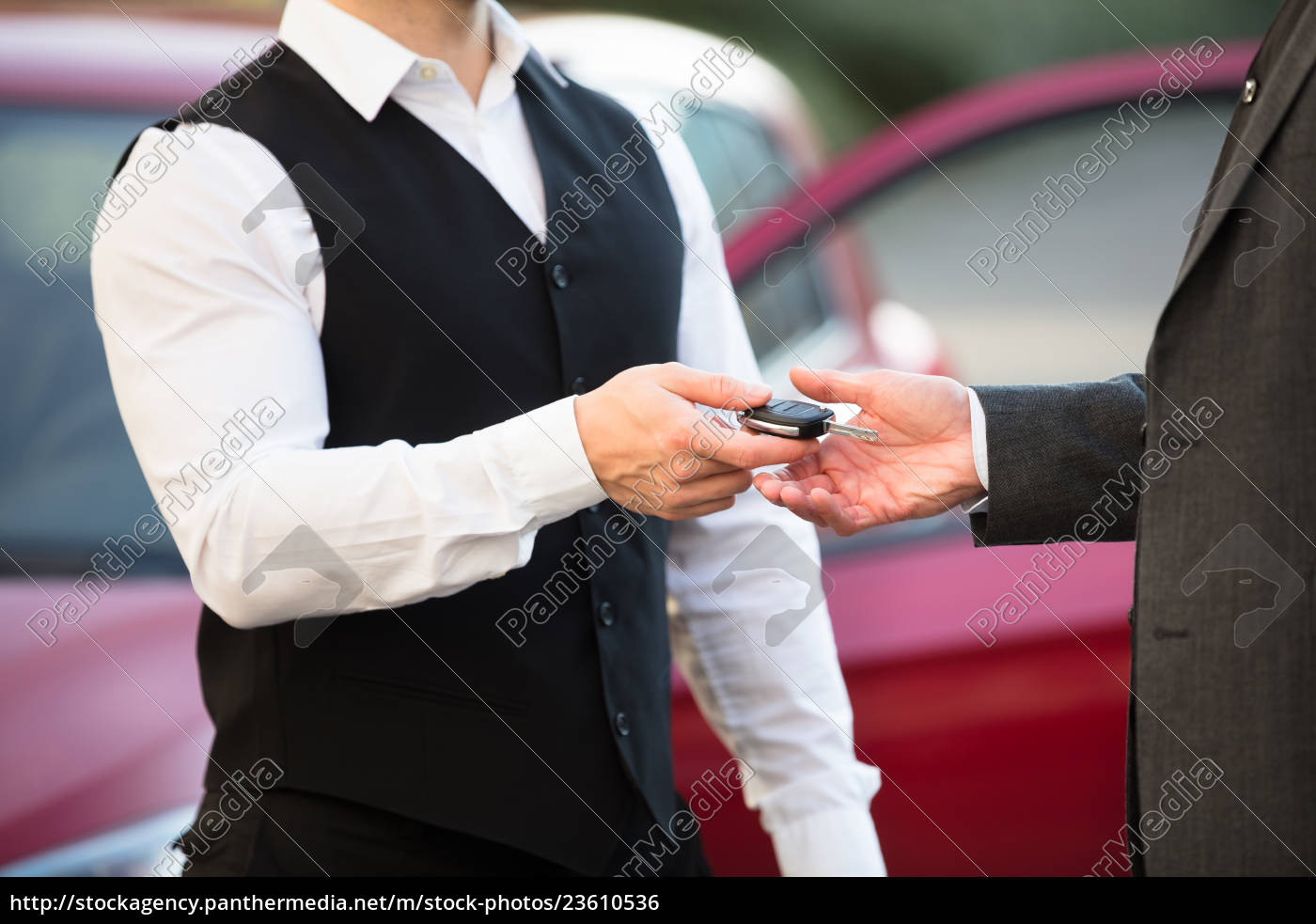 valet, giving, car, key, to, businessperson - 23610536