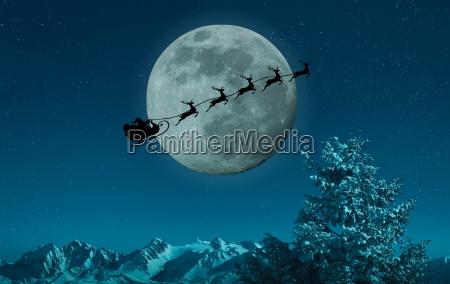 silhouette of santa and reindeer flying