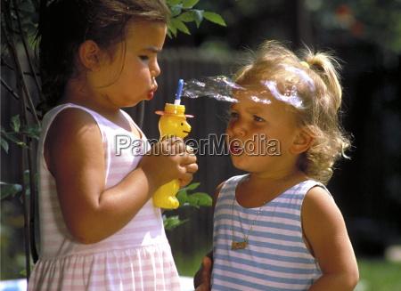 2 kleine maedchen spielen im garten