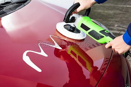 persons hand polishing car hood