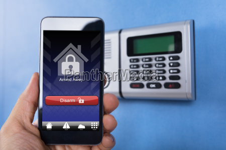 hand holding smartphone for disarming the