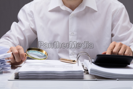 businessman, examining, invoice, with, magnifying, glass - 23618152