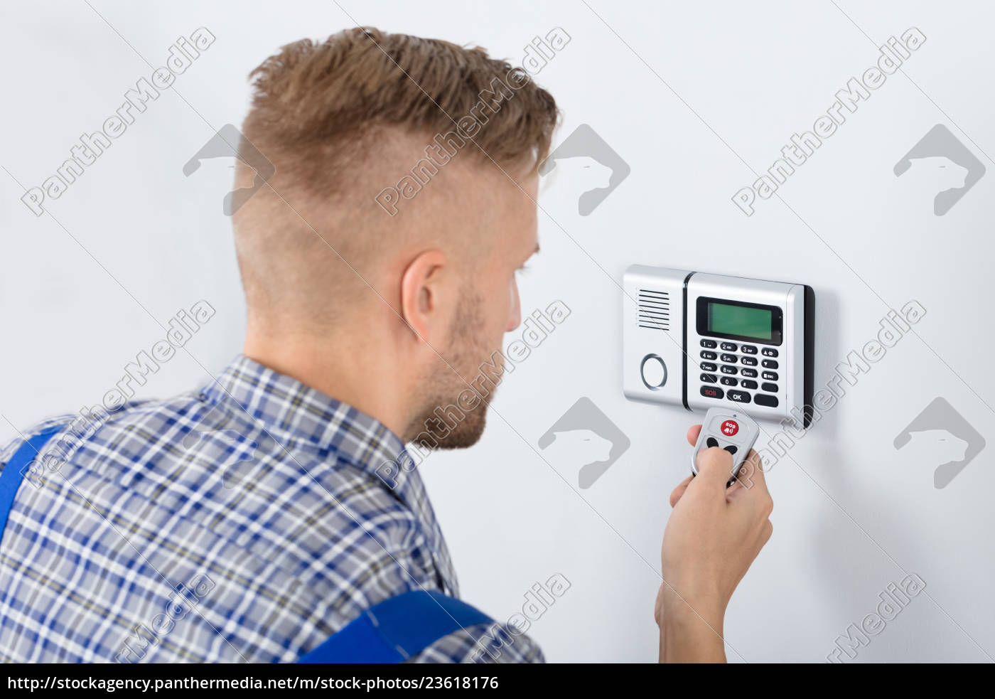 repairman, using, remote, to, operate, security - 23618176