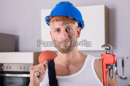 young, plumber, holding, wrench, and, plunger - 23618268