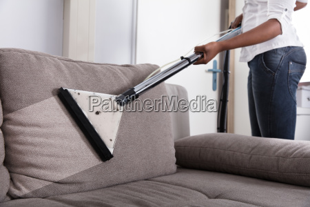 housewife cleaning sofa with vacuum cleaner