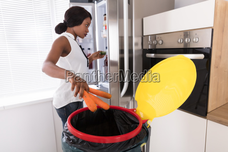 woman throwing carrot in trash bin