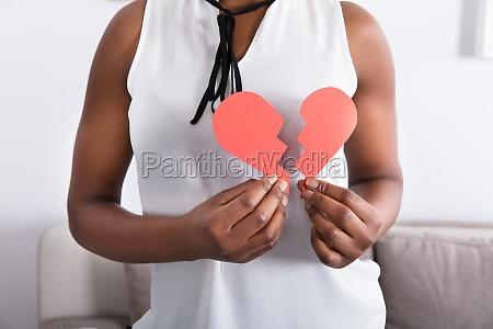 womans hand holding broken heart