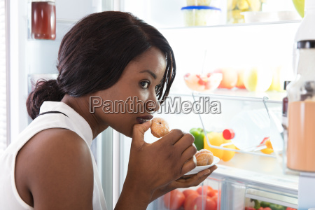 close-up, of, a, woman, eating, cookie - 23620410