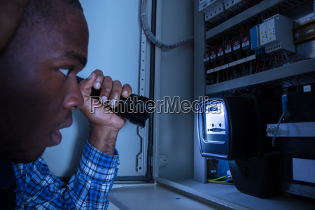 electrician, examining, a, electric, meter - 23620280