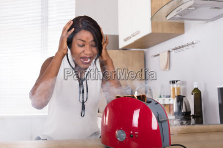 frustrated, woman, looking, at, burnt, toast - 23620344