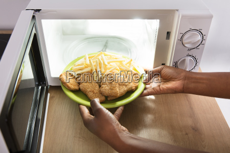 person, heating, fried, food, in, microwave - 23620422