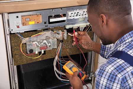 technician, fixing, dishwasher, with, digital, multimeter - 23620260