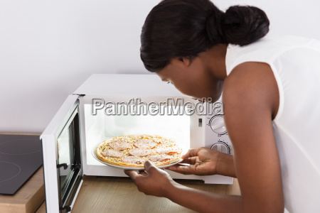 woman, baking, pizza, in, microwave, oven - 23620420