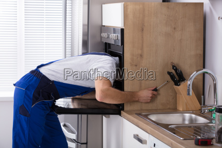 electrician repairing oven with screwdriver