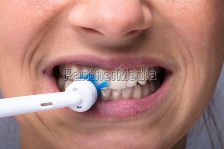 womans teeth with electrical toothbrush