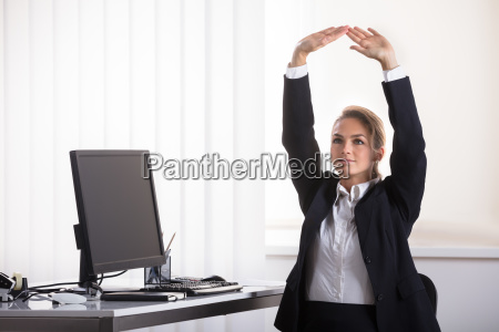 businesswoman sitting on chair stretching her