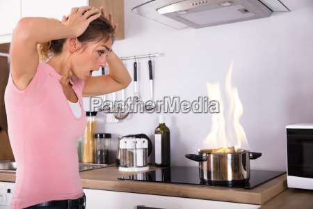 shocked, young, woman, looking, at, cooking - 23624148