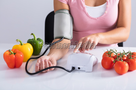 woman, checking, blood, pressure, on, table - 23624234