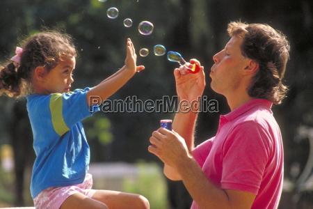 parkszene vater pustet seifenblasen waehrend seine