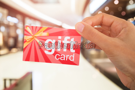 persons hand holding gift card
