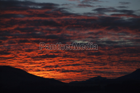 dramatic red sunset over silhouetted landscape