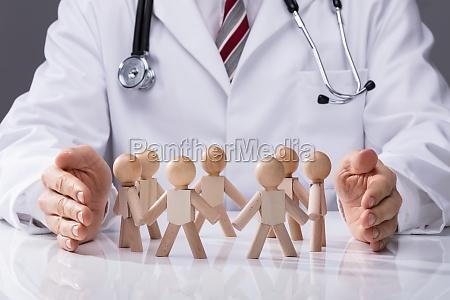 doctor protecting wooden figures