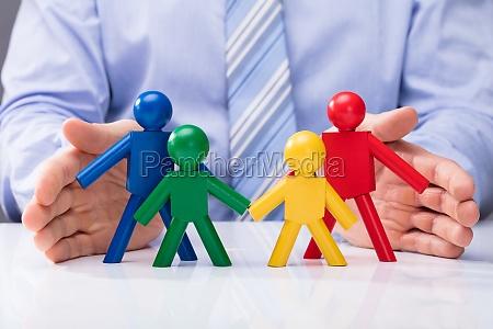 human hand protecting human figures