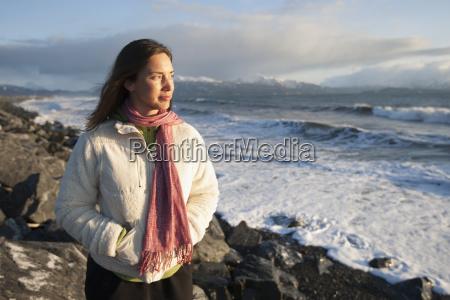 woman standing along the rocky shoreline