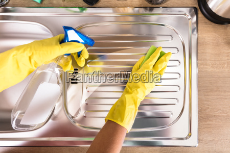 persons hand cleaning stainless steel sink