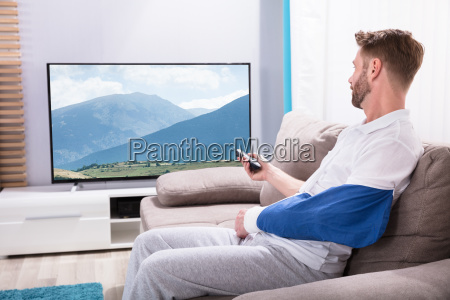 young man with fractured hand watching