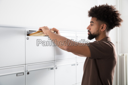 man putting letters in mailbox