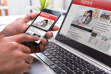 businessperson holding smartphone with online news