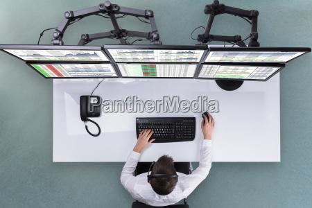 male stock broker analyzing graphs on