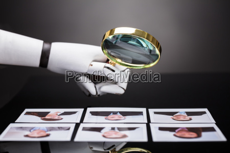 robot looking at candidate photograph with