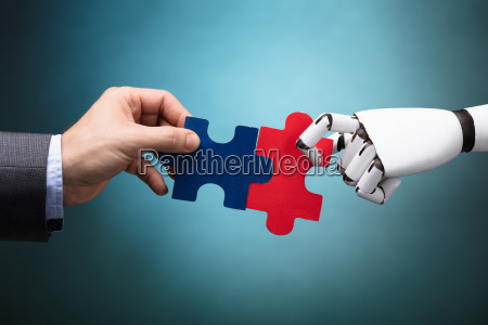 businessperson and robot holding jigsaw puzzle