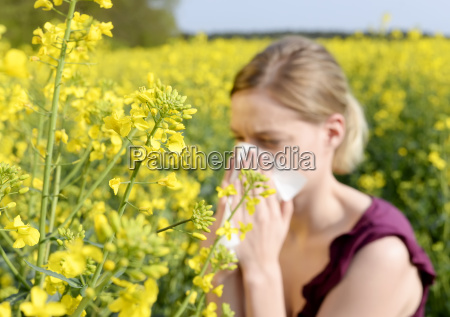 young woman sneezes