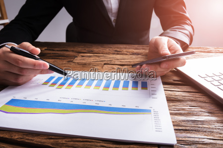 businessperson holding mobile phone analyzing graph