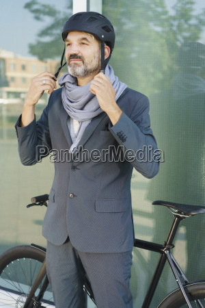 mature businessman wearing cycle helmet while