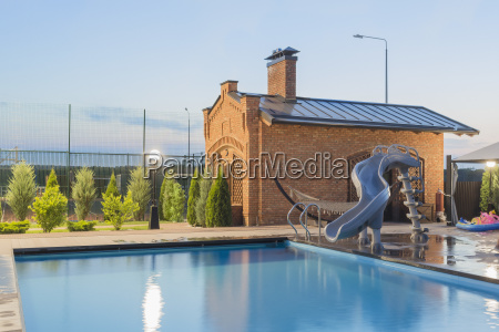 water slide by swimming pool in