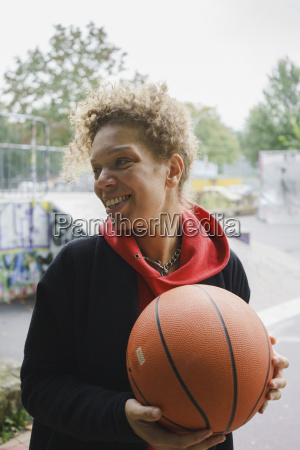 smiling mid adult woman holding basketball