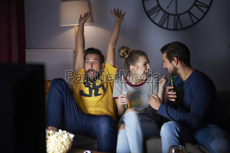excited friends sitting on the sofa