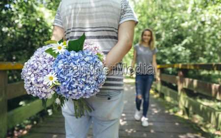 man holding a bouquet of hydrangeas